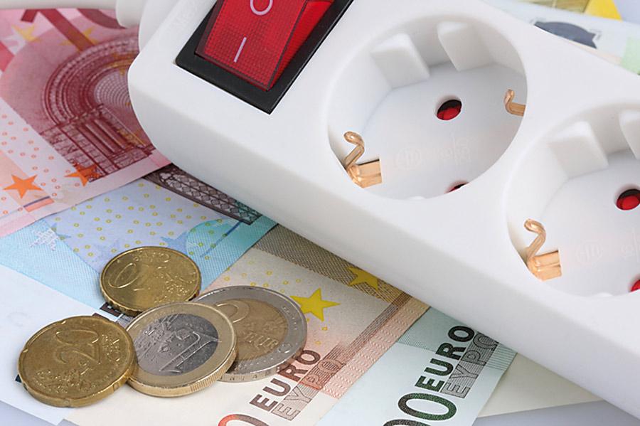 Foto Steckdosenverteiler liegt auf Geldscheinen und Münzen